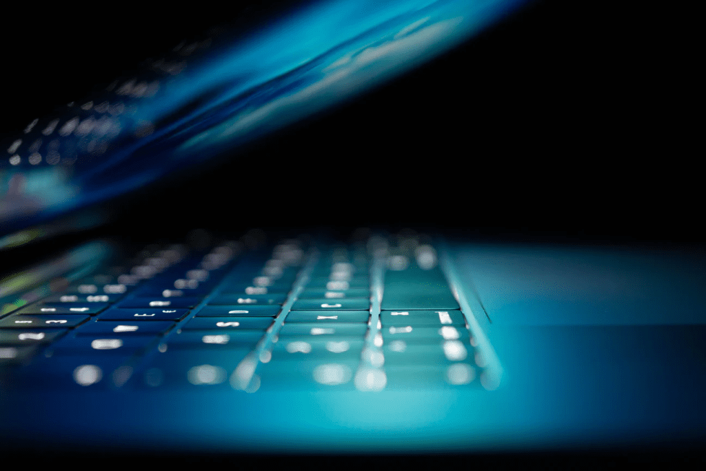 A side angle view of a laptop, only slightly opened, with keys illuminated.