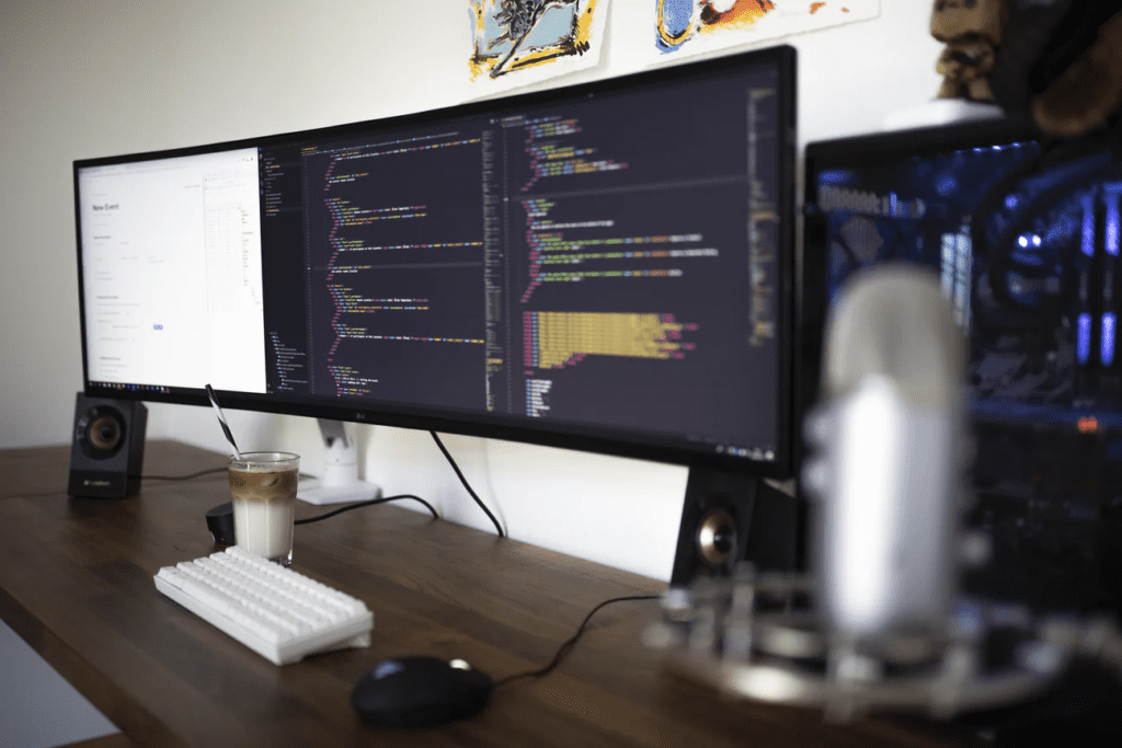 Computer monitors displaying code on a desk with a cup of coffee