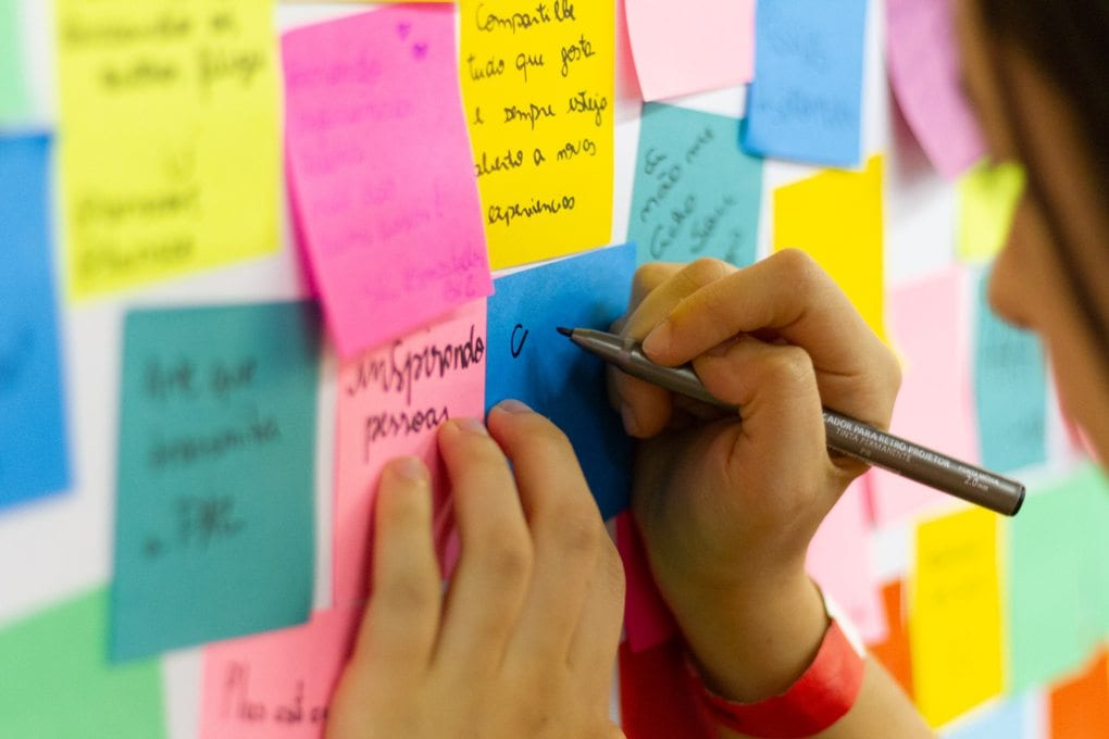 Person writing on a sticky note on a bulletin board