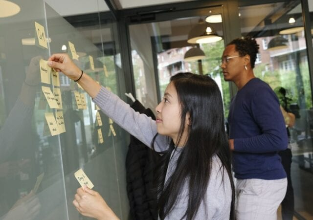 a man and woman using sticky notes on a board