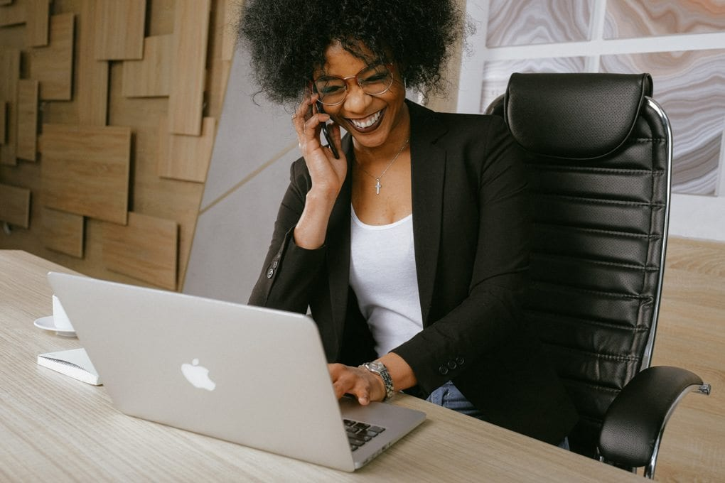 A person smiling and using a laptop during a business call.