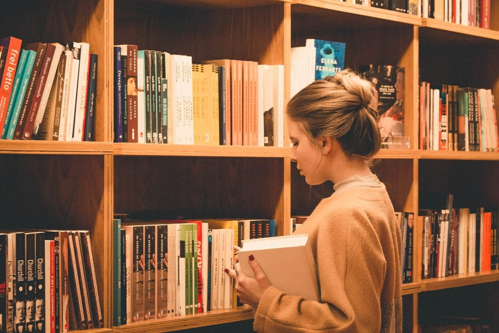 Woman stands in front of a large bookshelf, hold a book in right arm