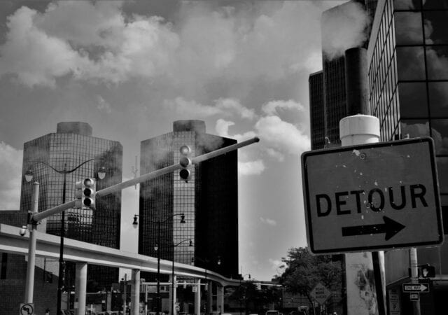 Greyscale City landscape with traffic signal and detour sign