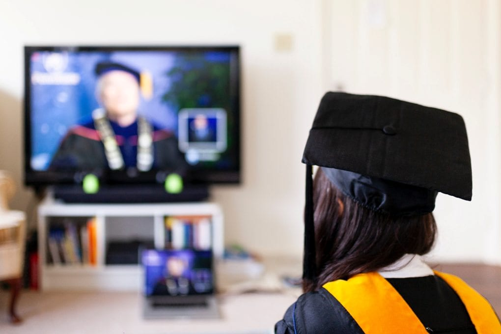 woman looking at the television while wearing graduation clothing