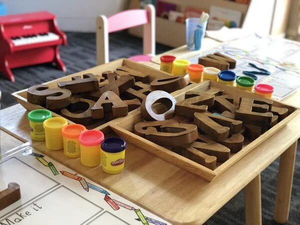 Cans of Play-Doh beside large wooden letters of the alphabet in a preschool setting.