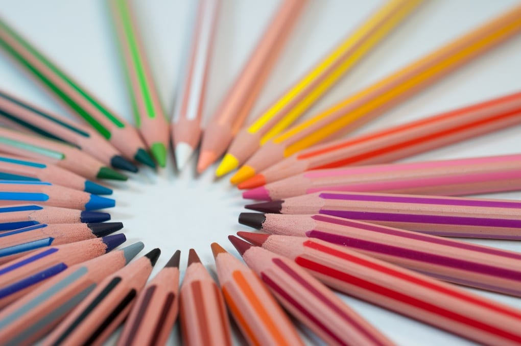 Colored pencils arranged in a circle on white background