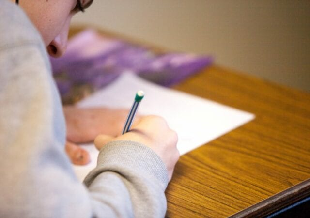 Student leaning over wooden desk and writing with mechanical pencil on sheet of paper
