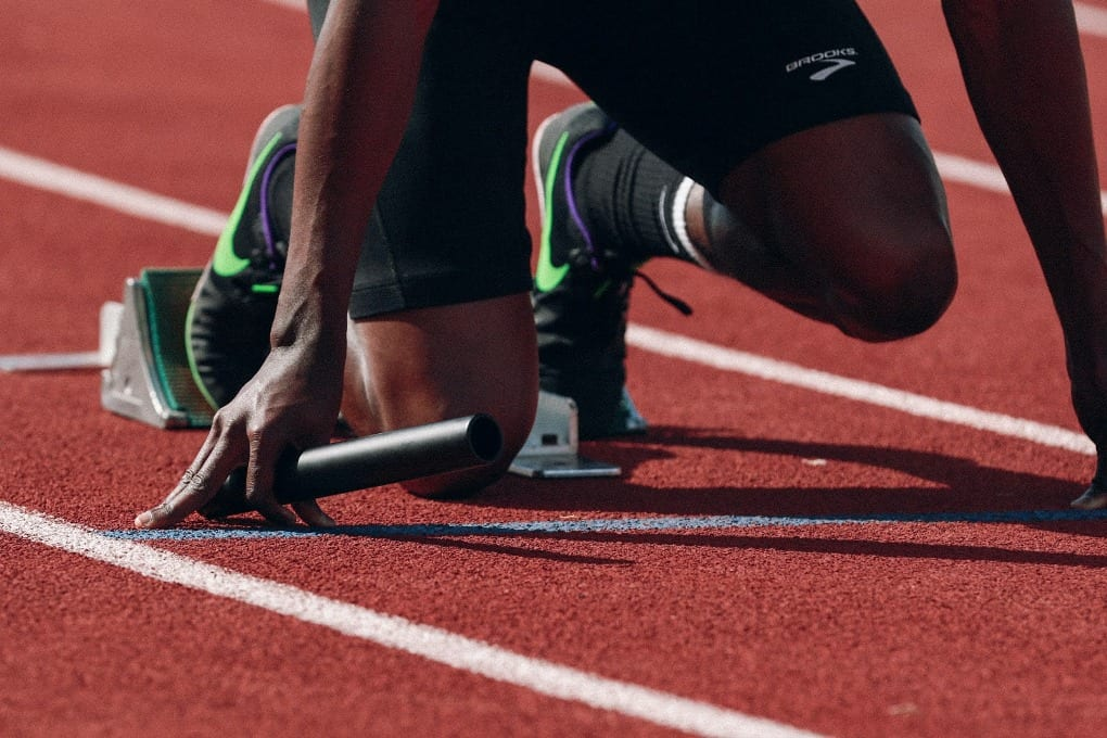 a close up of a runner's feet on the running track and his arms on the floor as he is about to race.