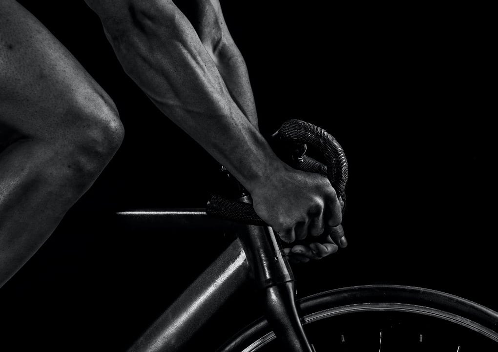 black and white photo of a cyclists arms and leg.
