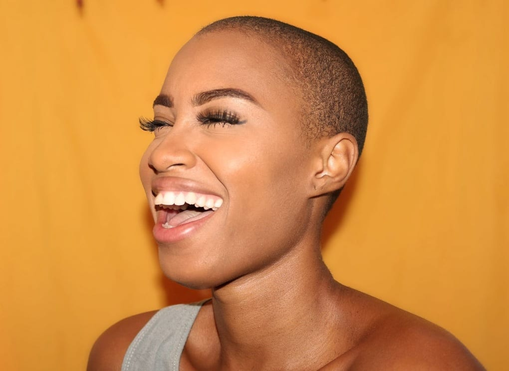 A woman confidently smiling and laughing with a nice orange background