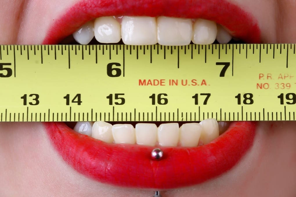 A woman's lips with a ruler between her teeth