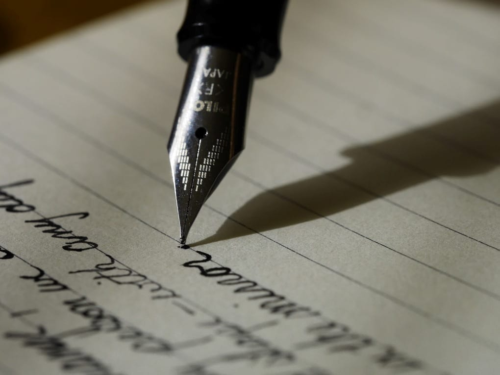 Calligraphy pen writing in cursive on lined paper