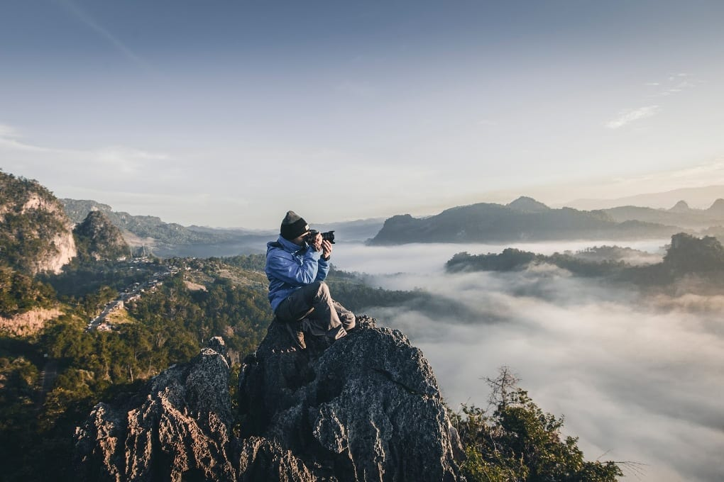 a man sits on a cliff top and photographs a misty mountain landscape