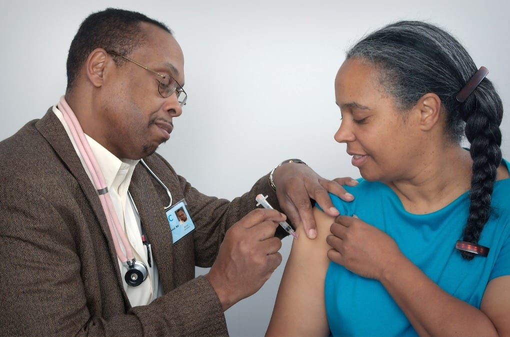 a doctor providing an injection to a patient