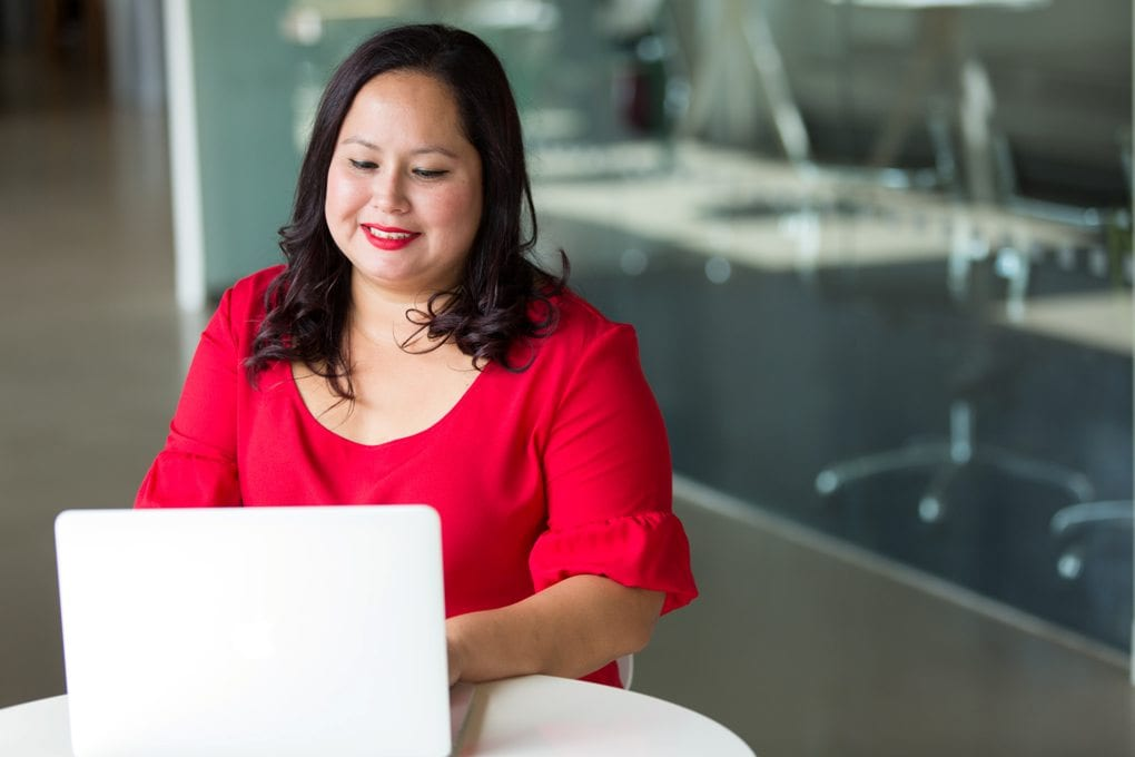 Woman in red blouse smiling and working on laptop