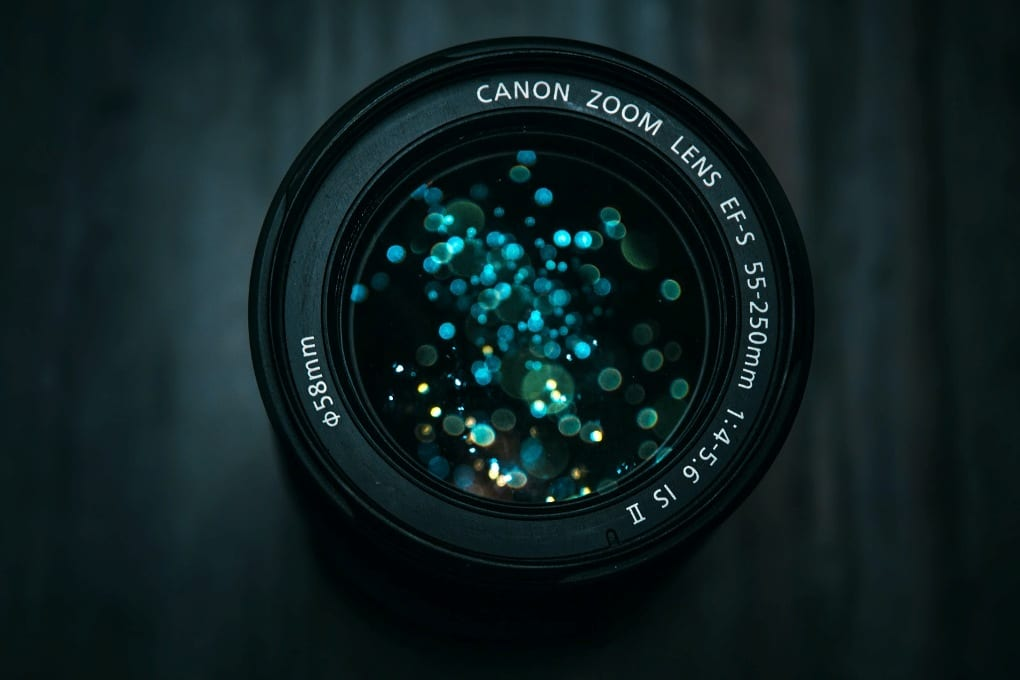 a close-up of an 85mm Canon lens with sparkling blue spots inside