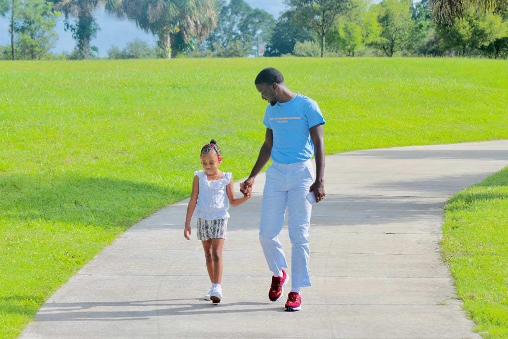 Man in blue t-shirt holding hands with little girl in white shirt and walking on sidewalk at park