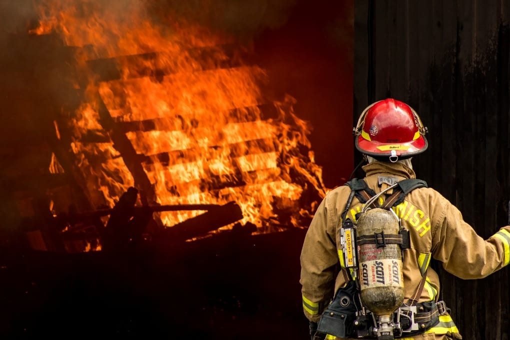 a firefighter standing in front of a wall of flames