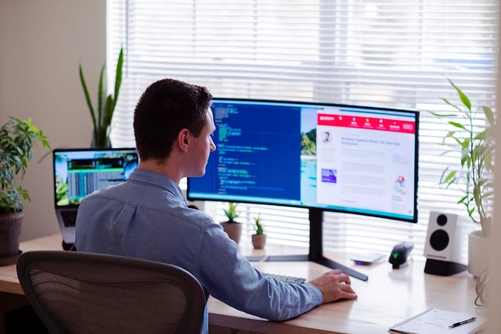 Man in blue dress shirt sitting in front of desktop monitor screen displaying code