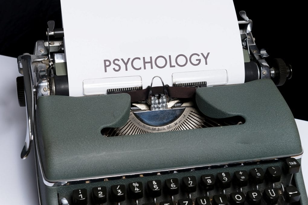 A typewriter with a sheet of paper on it that has the word psychology written on it.
