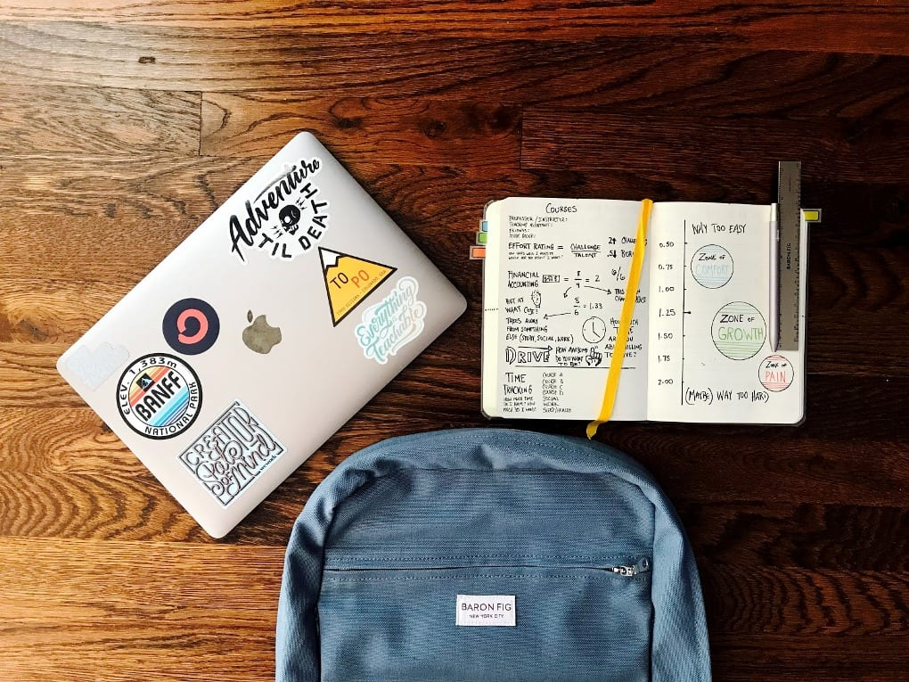 a laptop with stickers on it next to a blue rucksack and a notebook