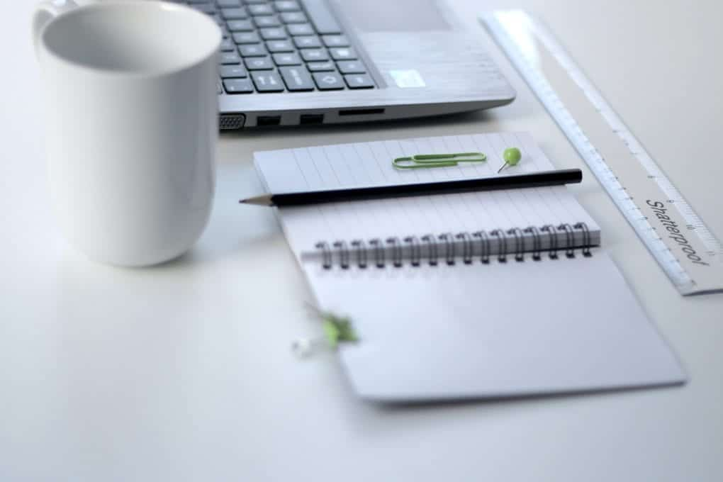 White desk with laptop and open notebook next to coffee mug