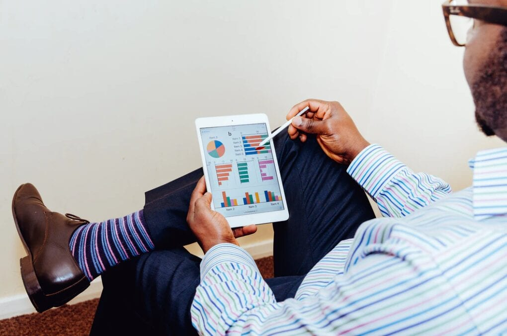 Man reviews business analytics and graphs on a tablet