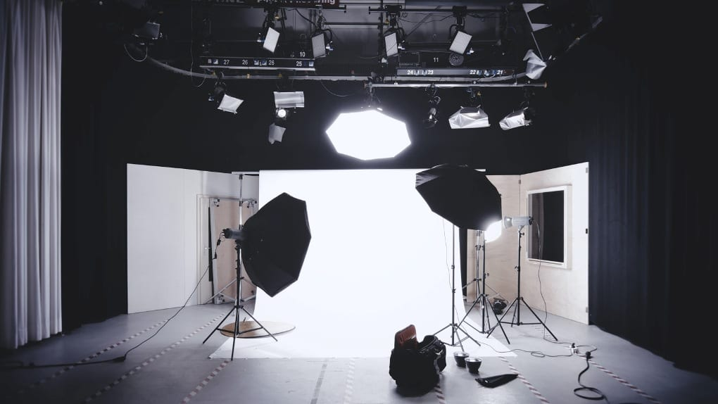 a wooden photography studio with light boxes and a white backdrop