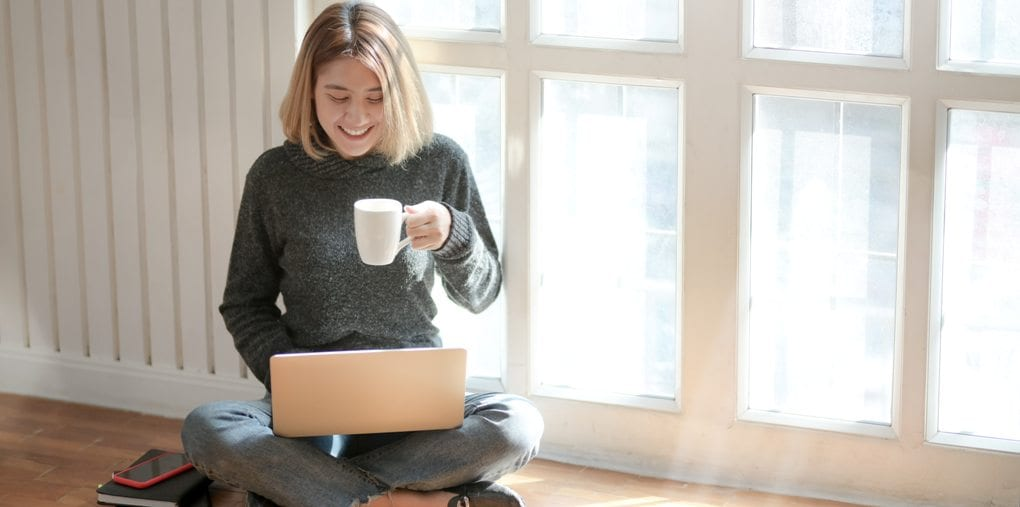 A woman in a gray sweater is smiling and using her laptop.