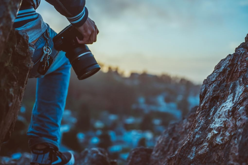 a man's leg stands on a rocky cliff with a camera on his hip