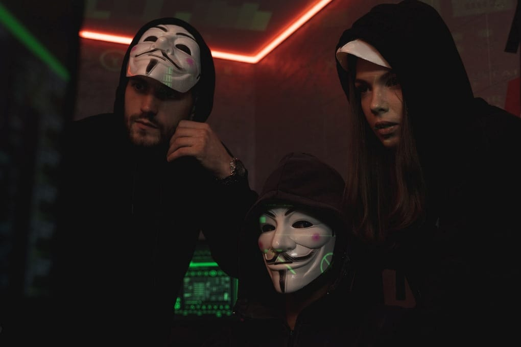 three hackers wearing masks in front of a computer