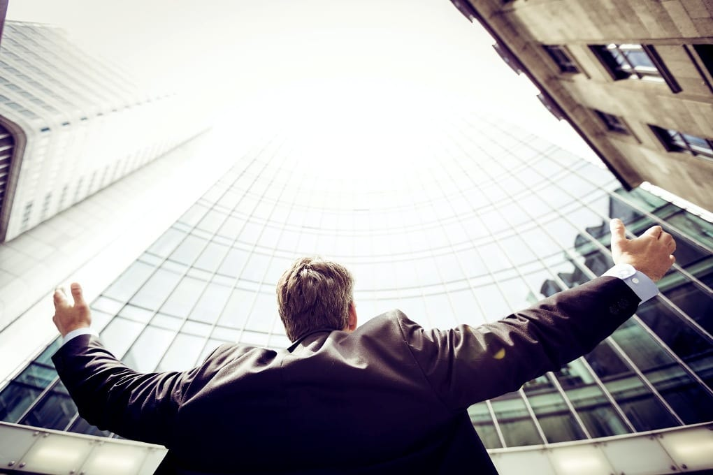 Man in suit raising arms above head and looking up at tall buildings