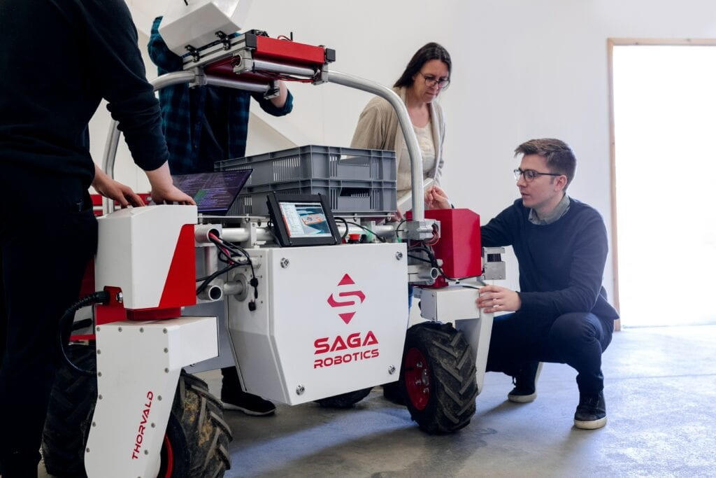 Man in black long sleeve shirt and blue denim jeans crouching beside a red and white industrial robot.
