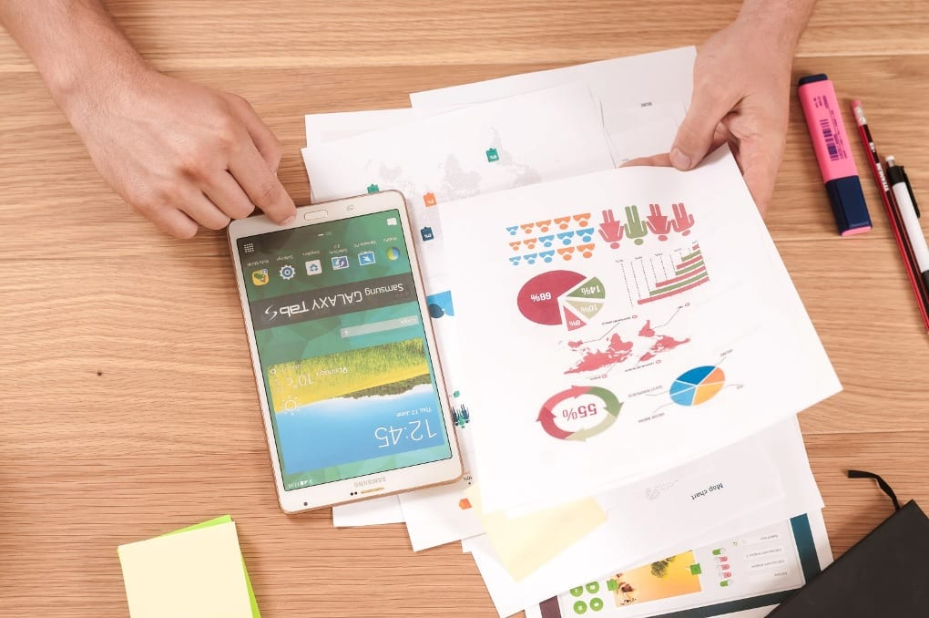 Person holding white paper with colorful graphs over wooden desk next to tablet