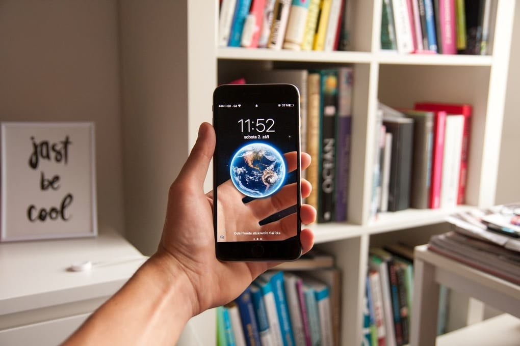 In a room with a large white bookshelf and other white furniture, a person's hand holds up an iPhone that shows a 3D image of Earth hovering above a digital reconstruction of the part of the hand that is, in reality, behind the iPhone.