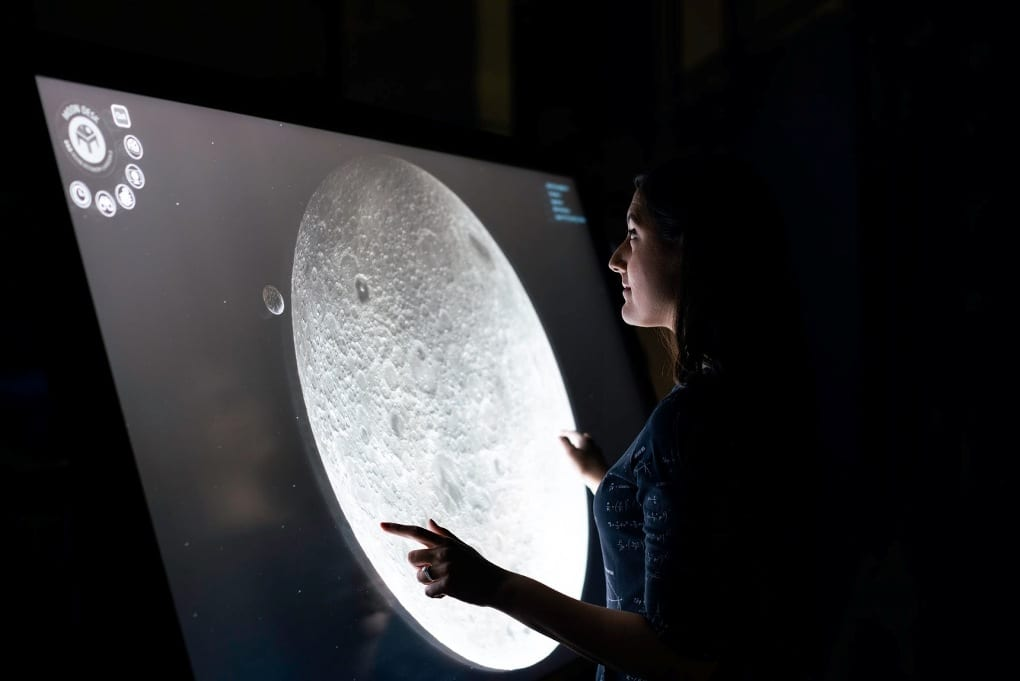 A woman studies a close-up image of the moon displayed on a large computer screen.