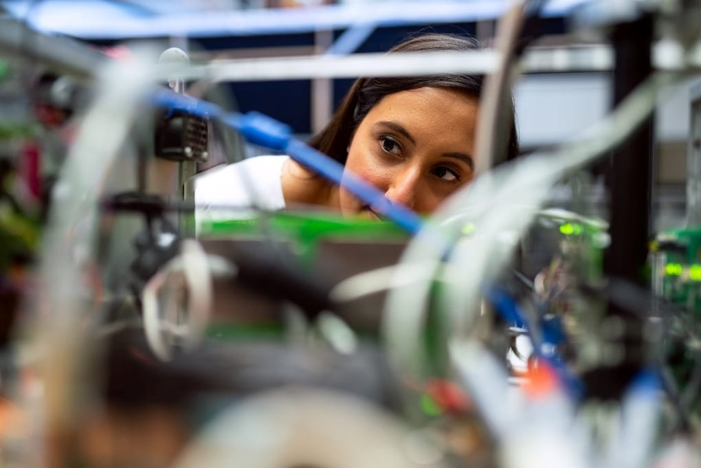 An engineer gets close to a machine to inspect its wiring and components.