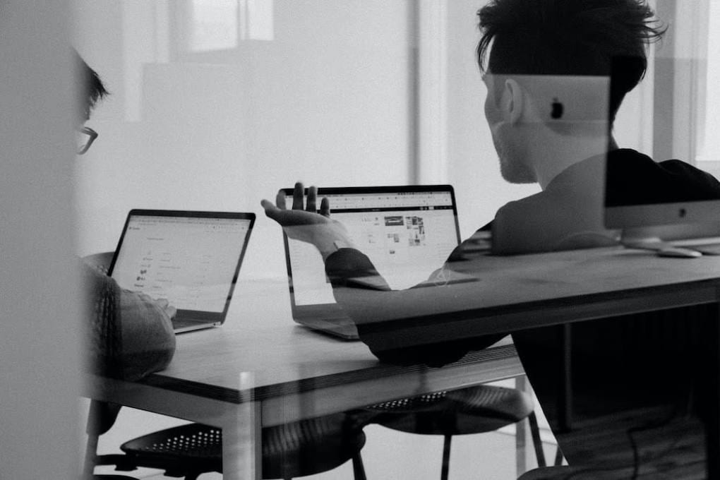 Through the window of a conference room, two people with their backs turned are seen discussing something on their laptop screens.
