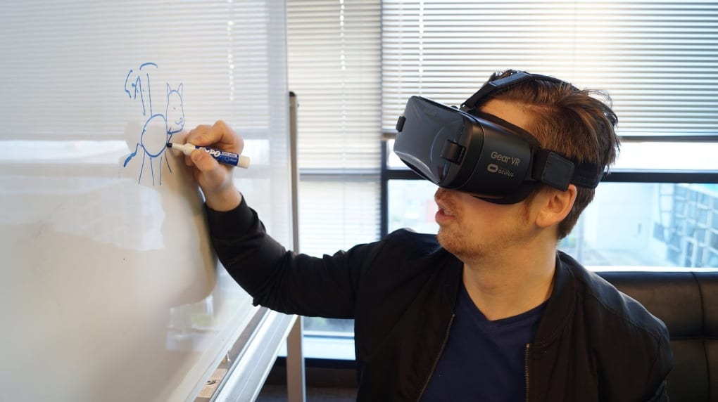 A man wearing a blue shirt, black jacket, and black VR headset draws a four-legged animal on a white board with a blue dry-erase marker.