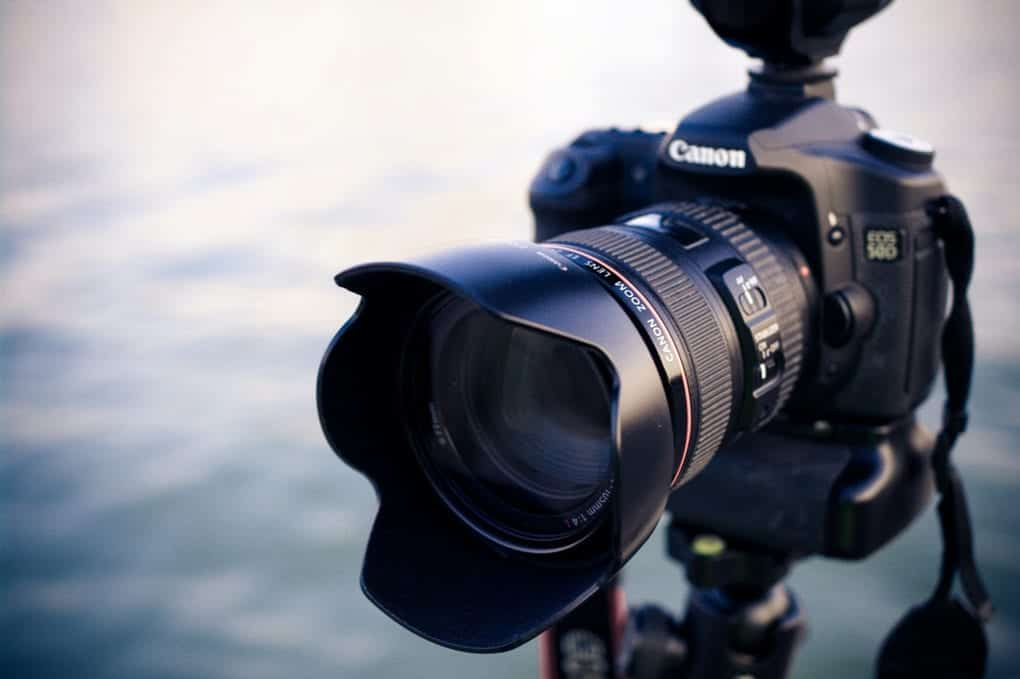 Black canon camera with large lens positioned on tripod