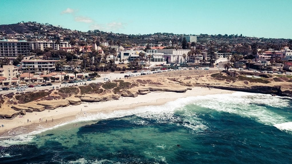 A shoreline view of La Jolla Beach in San Diego, with squat buildings, rolling hills, and tall trees scattering the background.