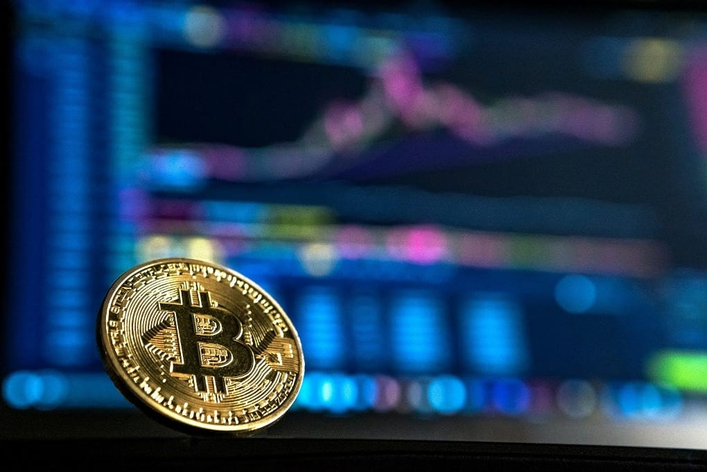a Bitcoin in front of an analytical graph background