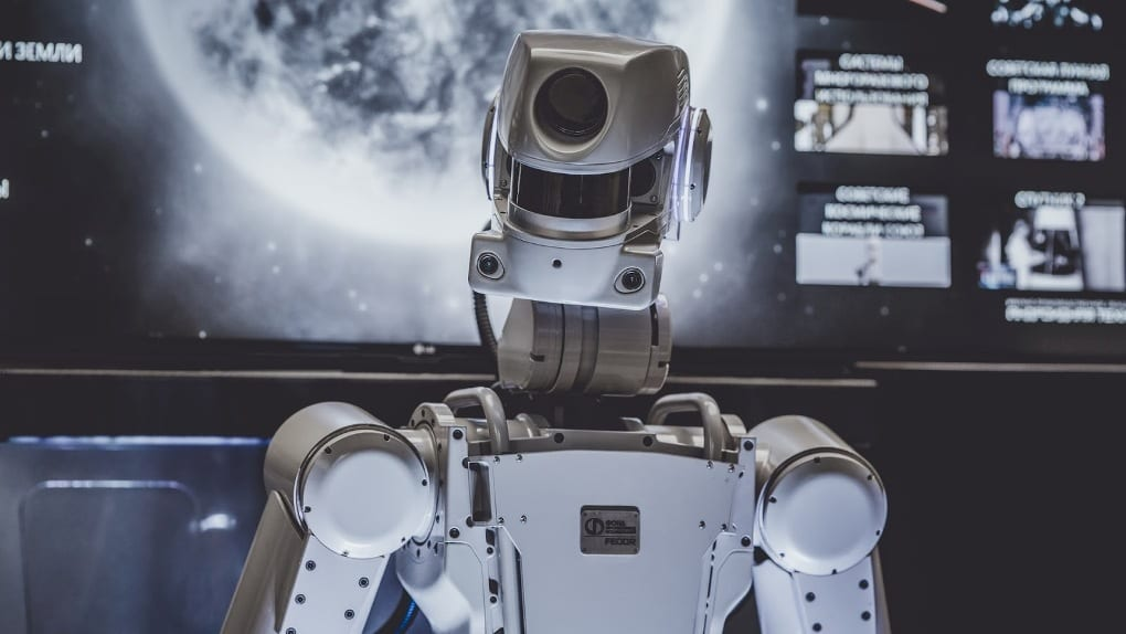 a white robot stands in front of a screen with the moon on it