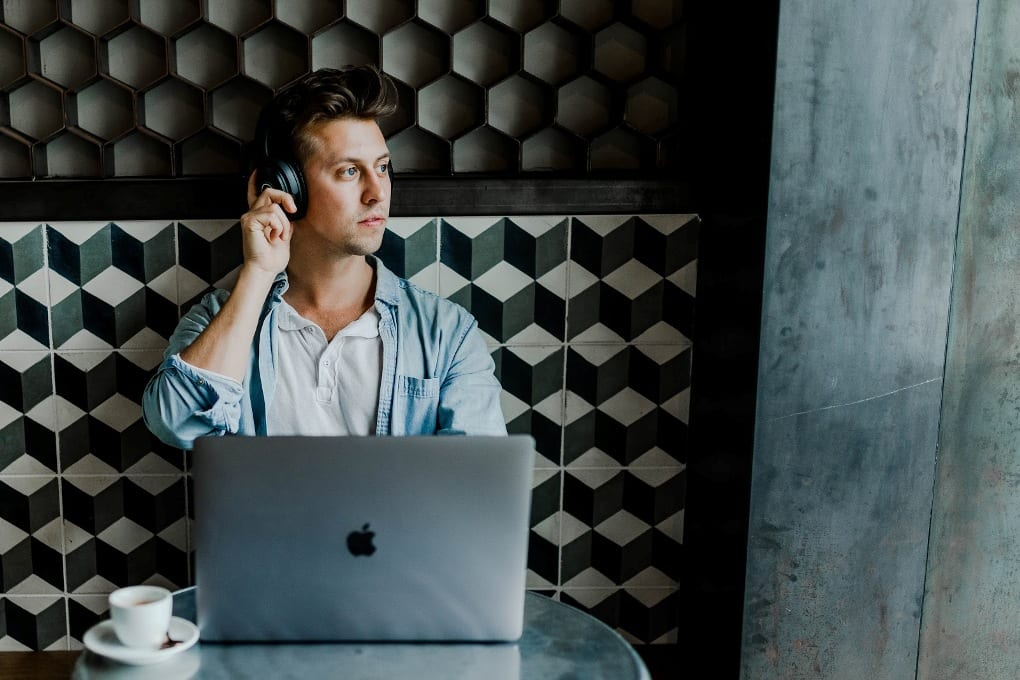 Man sitting against patterned wall wearing headphones and using laptop