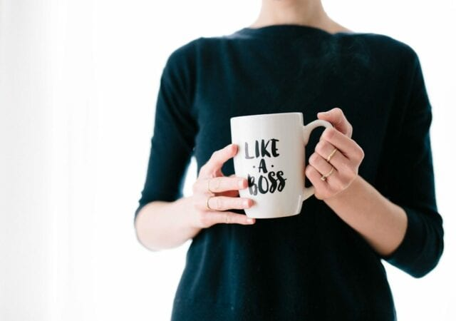 "Woman wearing black long-sleeved shirt and holding a white mug that says ""like a boss"""