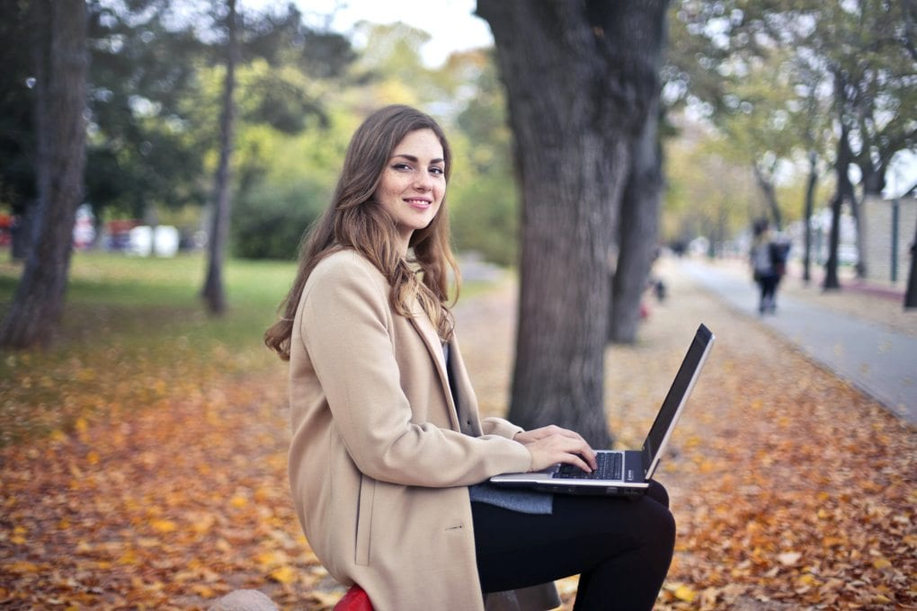 Smiling woman wearing a tan coat works on a laptop outside, with trees in the background and leaves on the ground behind her.