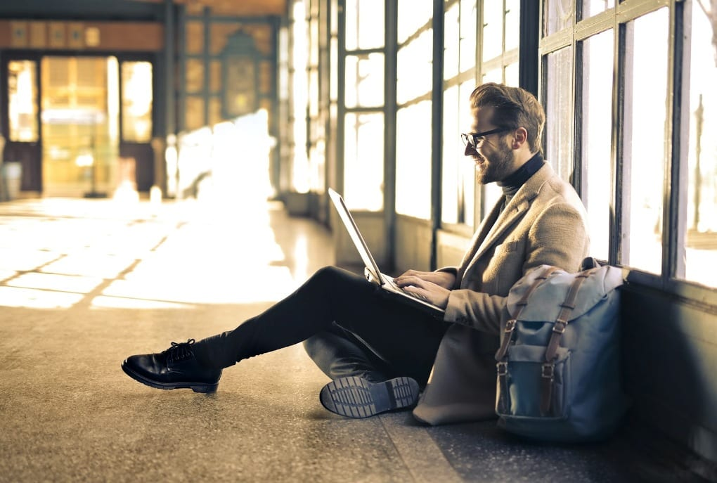 a man in a cream blazer sits next to his blue rucksack and types on his laptop