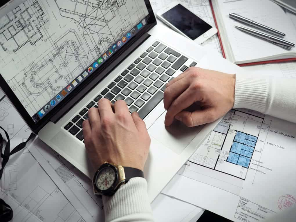 a person using a laptop to review blueprints