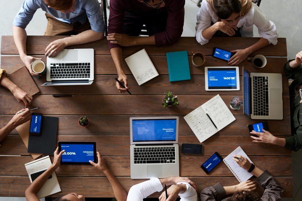Overhead view of a rectangular wooden table surrounded by eight people working on laptops, tablets, and smartphones.