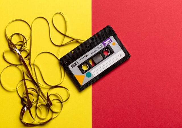 black cassette tape on a yellow and red background
